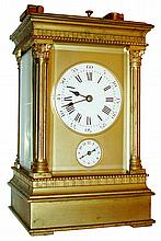 French hour repeating carriage clock with alarm, the gilt Anglaise Riche case with thick beveled glasses, Roman numeral white enamel dial and Arabic numeral alarm dial, dials with gilt mask, blued steel spade hands, polished brass movement with lever