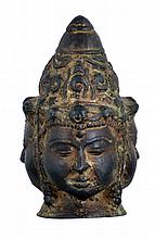 Asian bronze head representing unidentified Buddhist deity, composed of three identical faces, joined castings