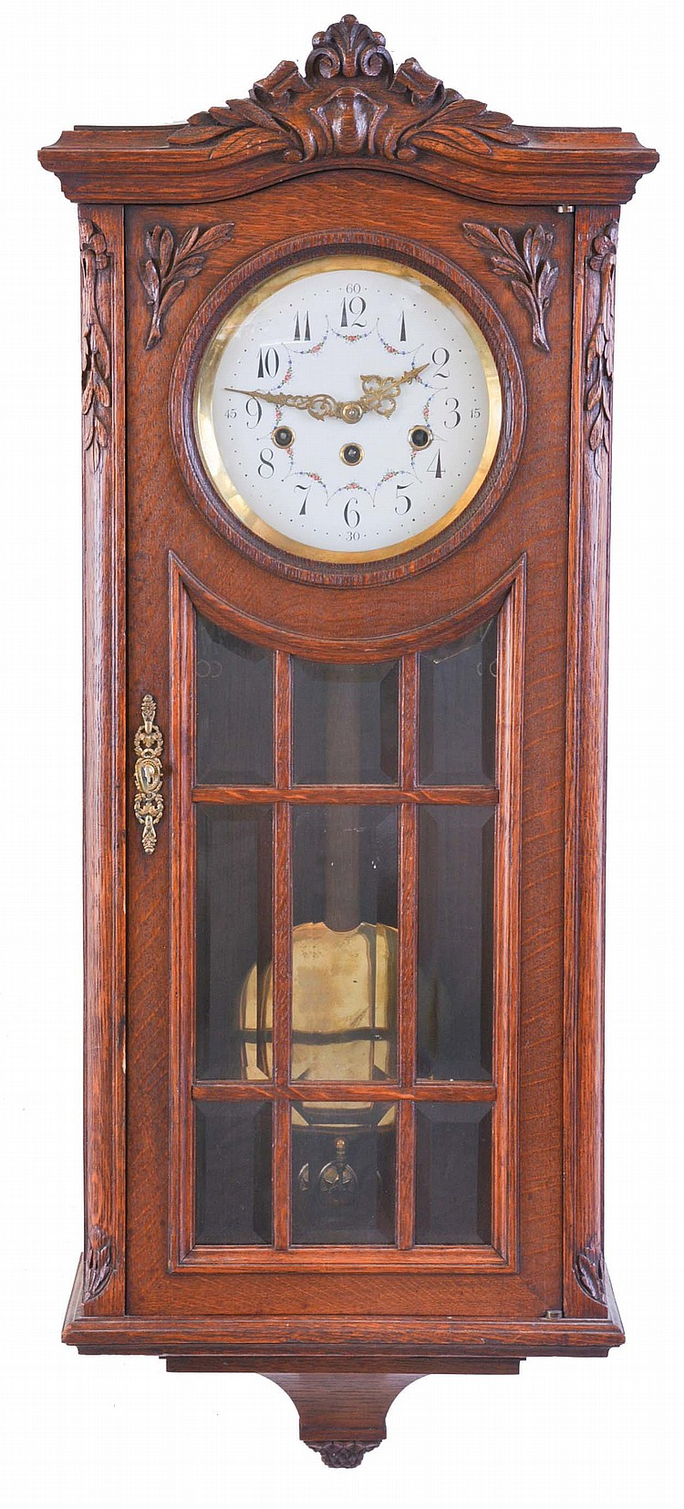 Junghans, Germany, a Westminster chiming wall clock, rectilinear oak case with carved ornament, door with 9 beveled glasses, Arabic numeral enamel dial with floral garlands and Louis XV style hands, 8 day, three train movement, with brass pendulum