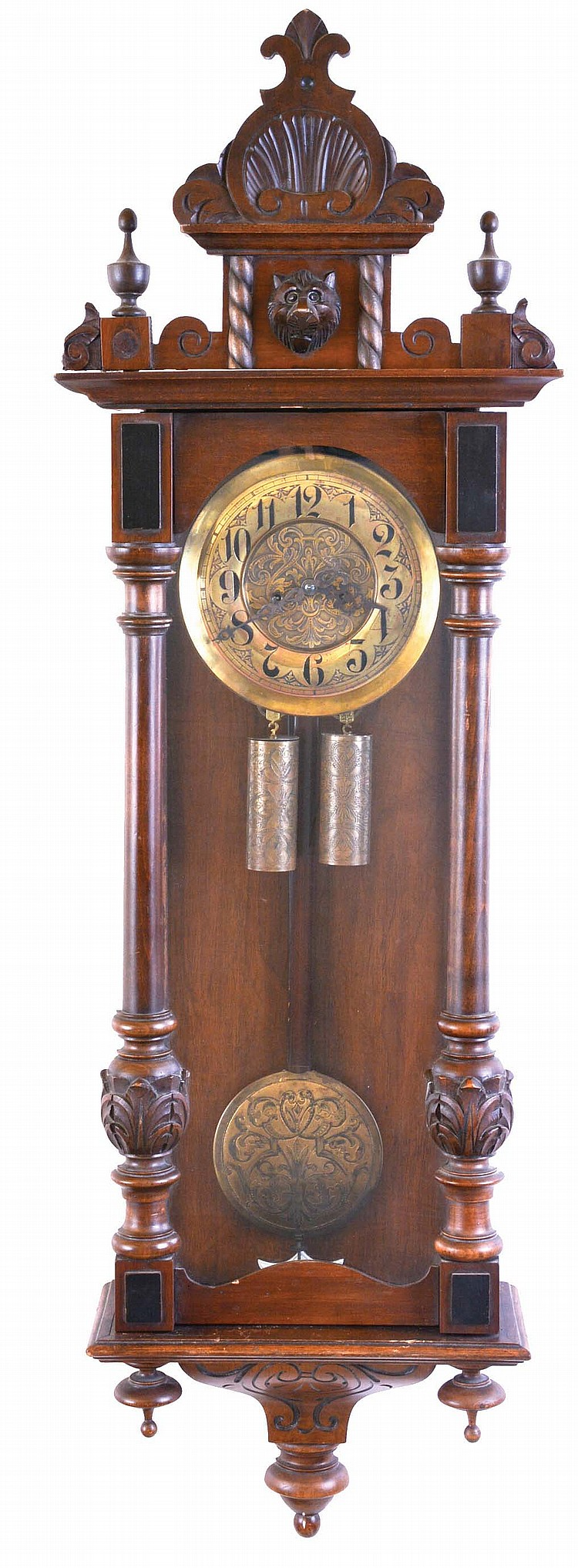 Gustav Becker, Freiburg, Germany, walnut case with turned and carved ornament, Arabic numeral, engraved brass dial, blued steel hands, 8 day time and strike movement, engraved brass pendulum and weights