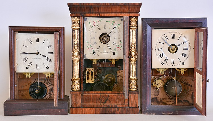 Clocks- 3 (Three): (1) Chauncey Jerome, New Haven, Conn. empire shelf clock with a spring driven 8 day time, strike and alarm movement in a rosewood veneered case with decorative gilt half columns, c1850. (2) Seth Thomas Clock Co., Thomaston, Conn.,