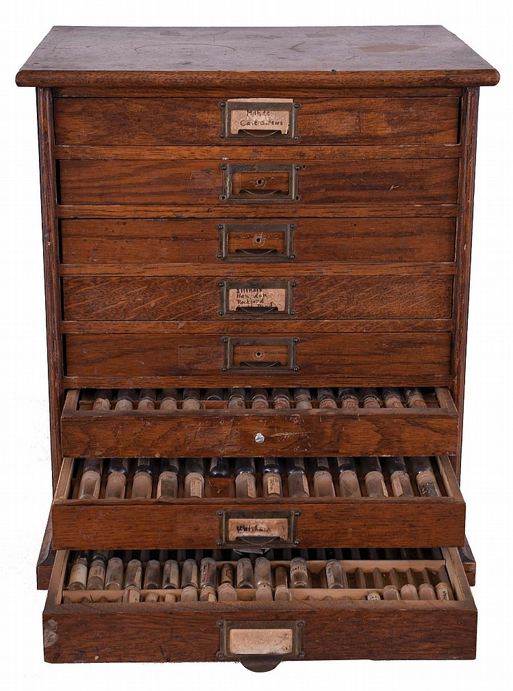 Watchmakers storage cabinet in oak, eight drawers fitted with trays to hold glass vials, and containing miscellaneous watch parts including screws, winding and setting parts, train wheels, and more