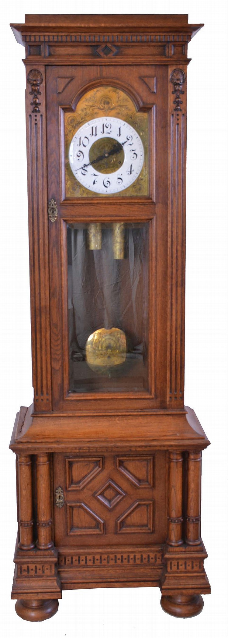 Germany, tall clock, 8 day, time and strike, two brass weight driven movement in a carved oak case, beveled glass door, cabinet in base on bun feet with engraved brass dial with white enamel chapter ring and matching engraved weights, pendulum and