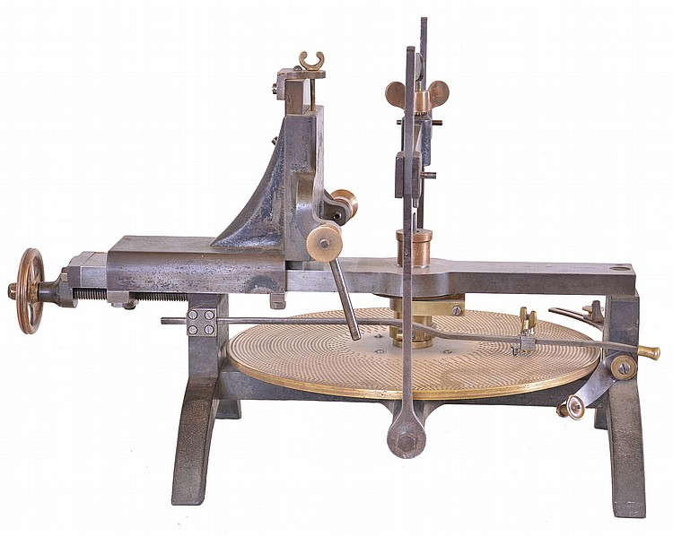 England, clockmakers wheel cutting engine, cast iron frame with screw feed adjustment for positioning cutting spindle, adjustable gallows, and brass dividing plate with 33 rows of holes, numbered 40- 300, and four additional rows of holes on plate