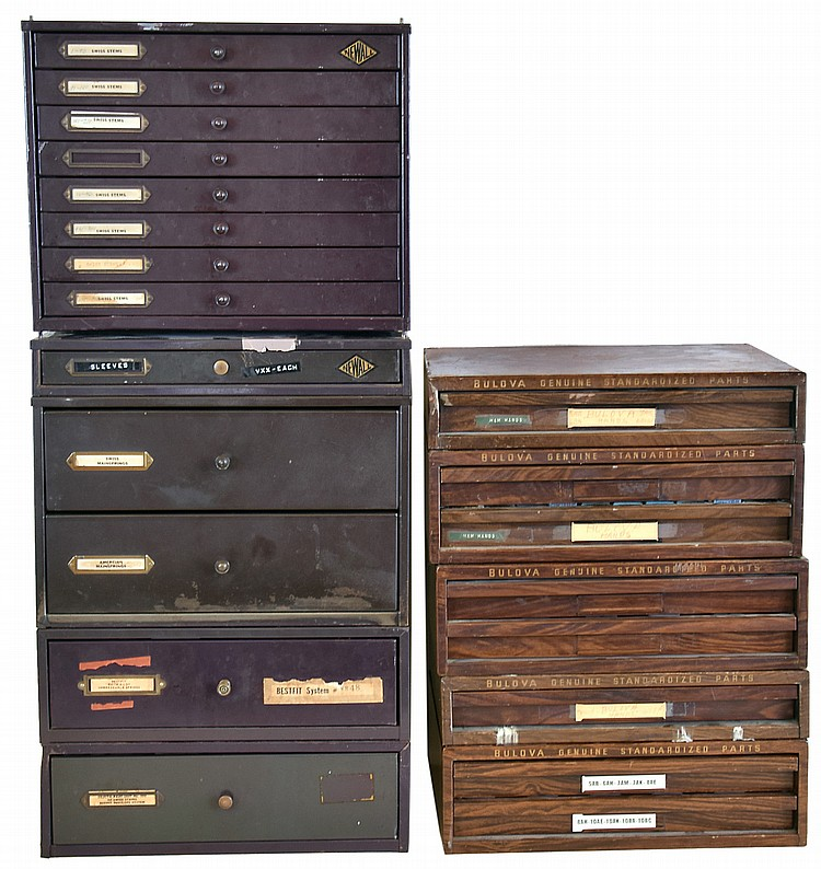 Watch parts, ten metal drawer units of factory- packaged wristwatch material including mainsprings, staffs, hands, clicks, crownwheels, and stems. Company names include Bestfit, Bulova, and Newall.