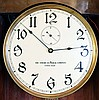 Clocks- 2 (Two) 8 day wood case wall clocks: Gustav Becker time and strike weight driven movement in later simple case with modern dial; American Clock Company, Chicago, self- winding wall clock