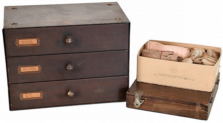 Two watch crystal cabinets with contents, the first a metal cabinet with three drawers, containing an assortment of crystals for wrist and pocket watches, the other a wooden box with wrist watch crystals, together with a small box containing mostly