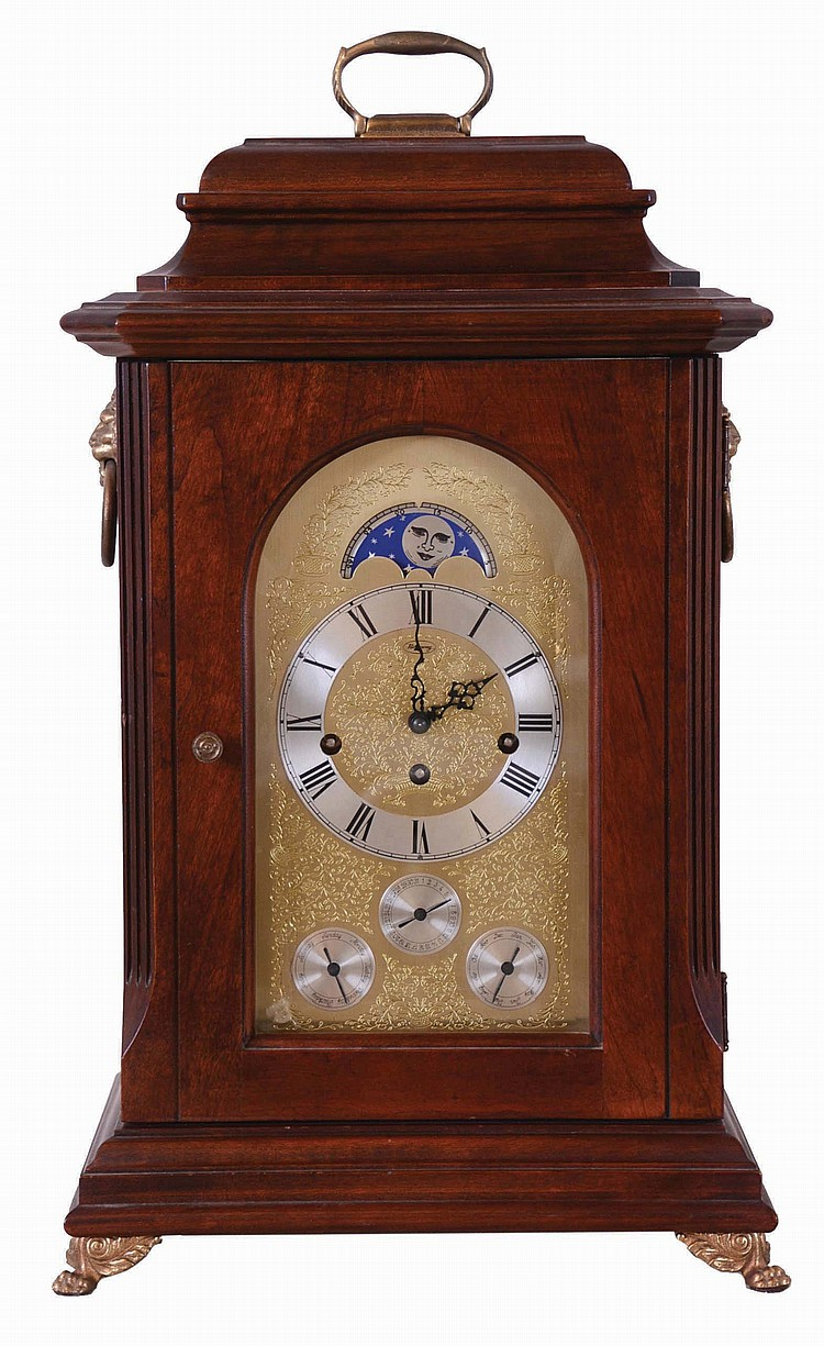 Unknown American mfg bracket clock, with Franz Hermle Westminster chime and calendar movement, and with rolling moon in the arch of the embossed dial. Case with mahogany finish, and with cast feet, handle and side lions. Day of week, date and month