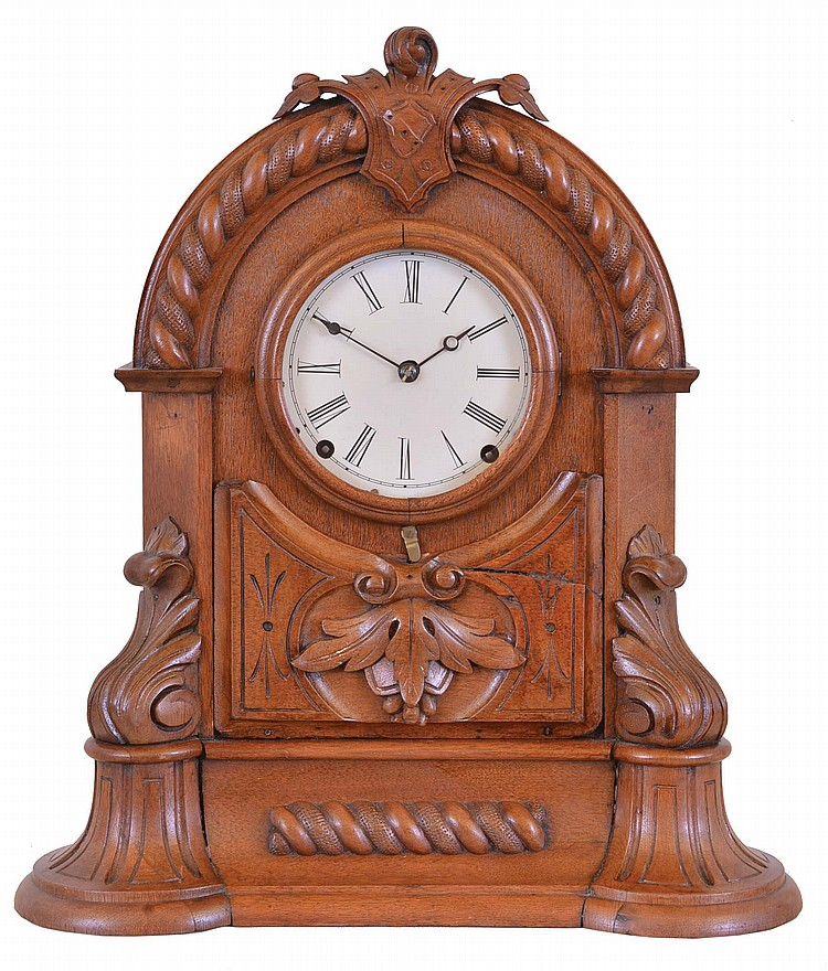 American Clock Co., 3 Cortlandt St. N.Y., shelf clock, walnut case with arch top, decorated with bold turned and carved elements, Roman numeral white enamel dial, blued steel hands, and 8 day time and strike Seth Thomas movement with lyre plates