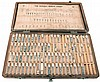 LaRink wood case of 15 stacked wood boxed assortments of Swiss and American labeled watch parts including jewels, staffs, seconds hands, mainsprings, crowns, stems for Bulova, Benrus, Greuen, Wittnauer, etc.