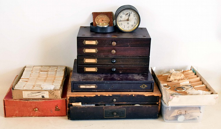 Watch parts and material: includes new / old wristwatch cases, crystals, movements, mainsprings, crowns, staffs, stems. Most in original packaging and drawer units. Also glass clock crystals, and one painted glass dial for electric advertising clock