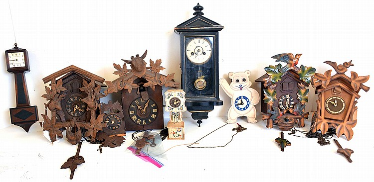 Clocks- 8 (Eight) German / Black Forest and novelty wall clocks: four cuckoos, a miniature Vienna spring driven, a miniature New Haven banjo, a miniature cuckoo and grandfather clock and a moving eye novelty wall clock