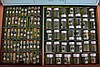Assortment of 25 watchmakers storage cabinets and boxes, many with parts, including jewels, screws, barrels, winding and setting parts, train wheels, balances, and more