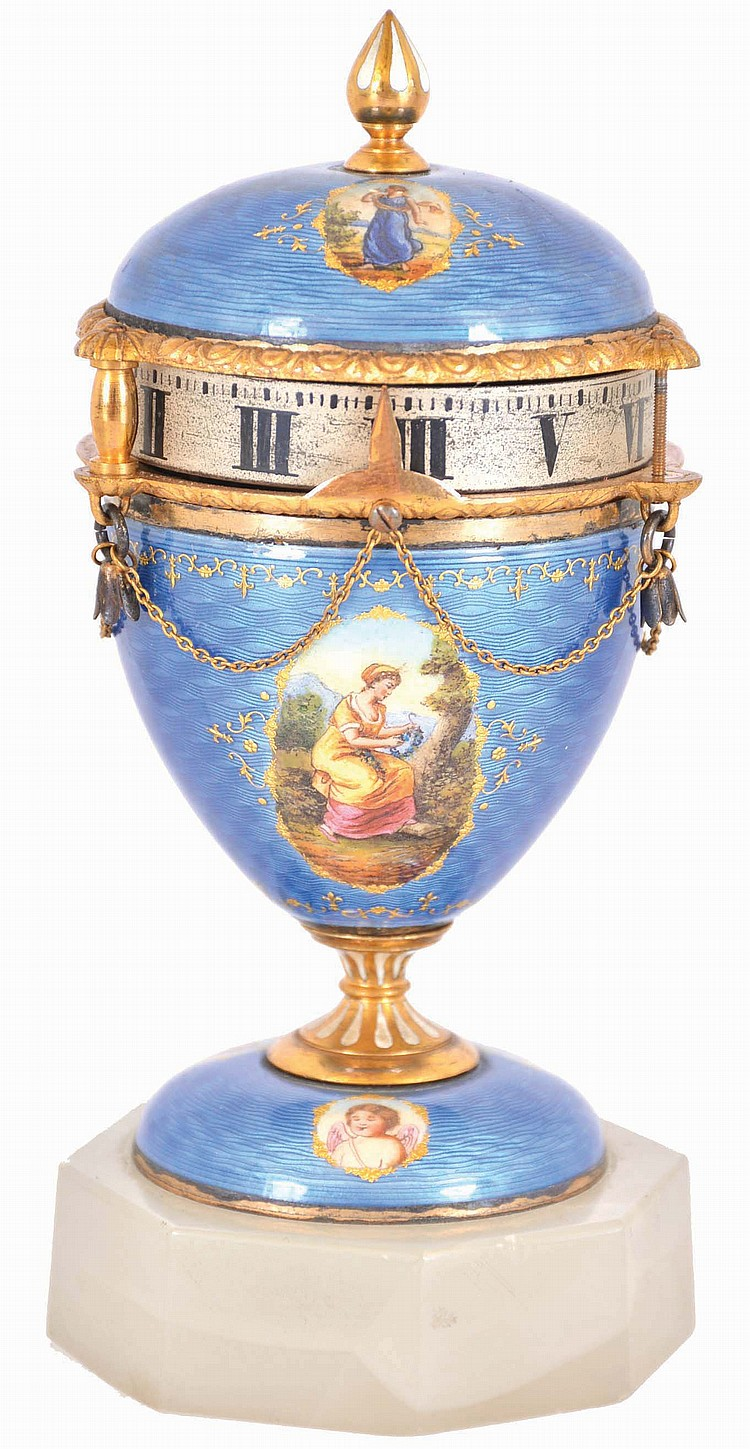 Switzerland, miniature urn form annular clock, the case with blue guilloche enamel and gilt molding, decorated with 7 paillon framed polychrome enamel portraits, the finial and stem with white enamel accents, and Roman numeral silvered dial, all on