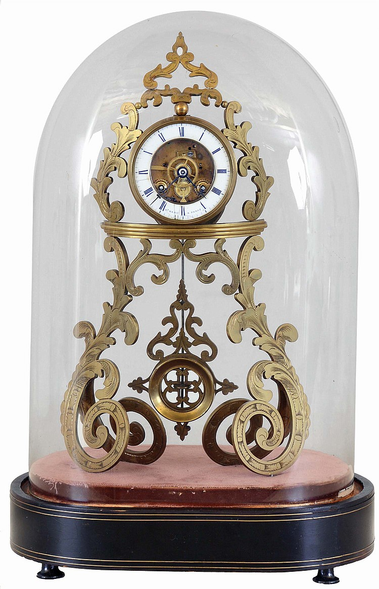 Hy. Marc, a Paris, table or mantel clock with skeletonized case and dial, pierced and engraved, scroll form brass case, pendulum similarly pierced and decorated, and also showing Gothic influence, signed Roman numeral white enamel dial, blued steel