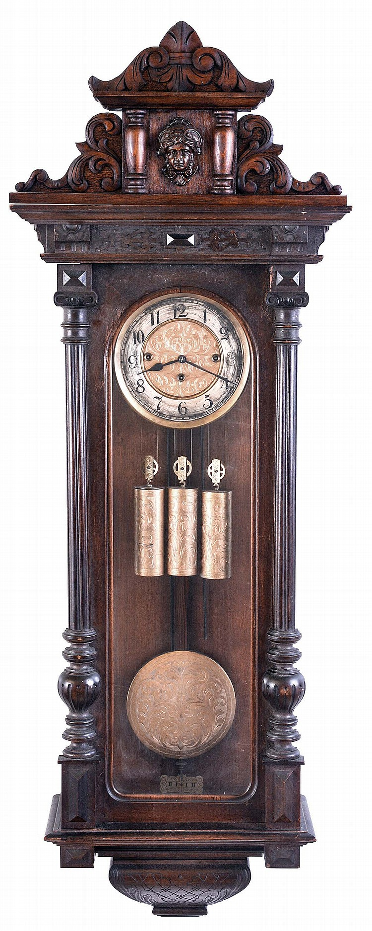 Gustav Becker, Freiburg, Germany, grand sonnerie hanging regulator, walnut case with turned and carved ornament, and frieze with blind fret, Arabic numeral silvered dial with gilt, engraved center, the pendulum, pulleys, and weights also engraved,