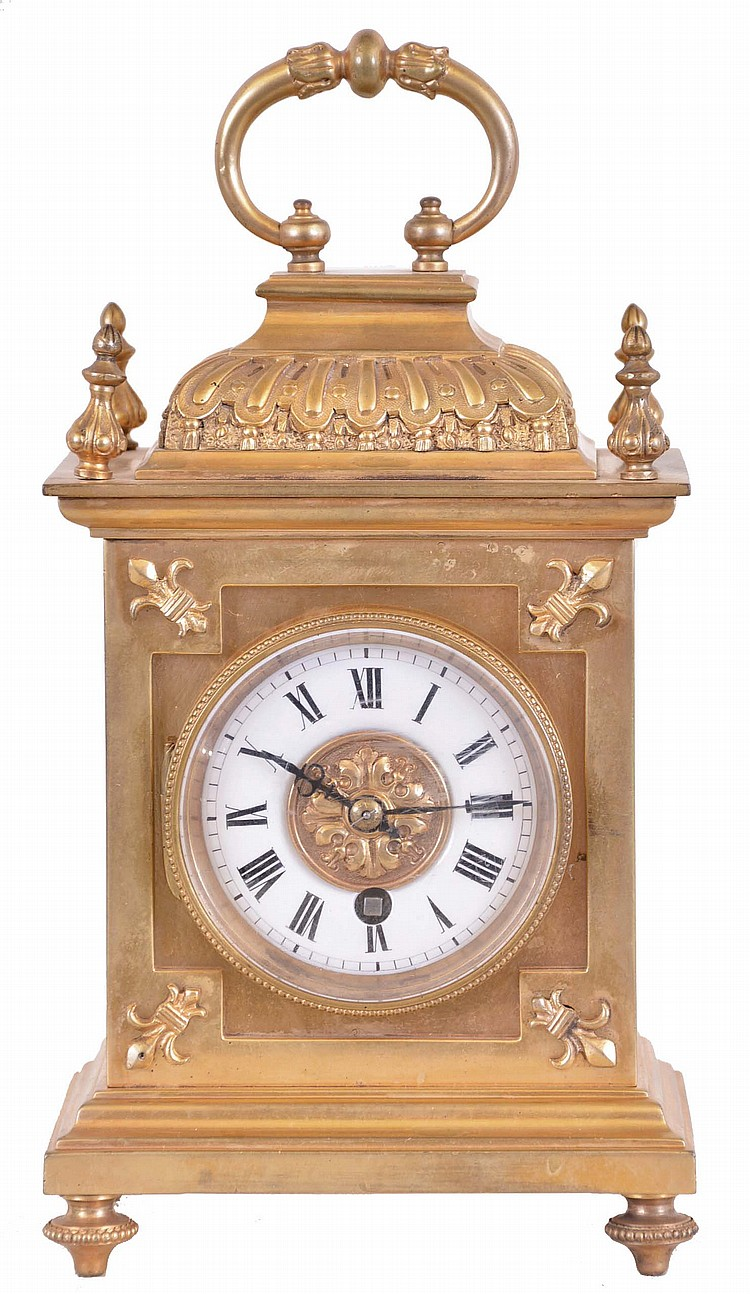France, gilt bronze desk clock, the decorative case ornamented with fleur de lis, finials, gadrooned cushion to, and carrying handle, Roman numeral white enamel dial, blued steel hands, 8 day timepiece movement with lever platform