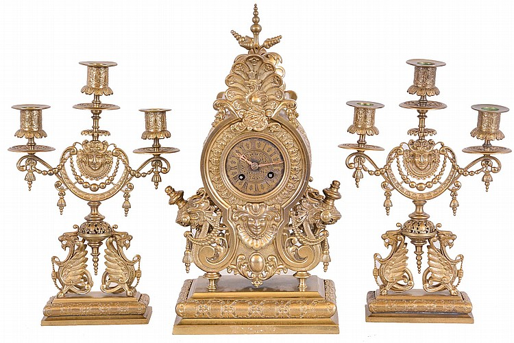 Lenzkirch, Germany, a three piece mantel garniture, ornate cast case with gryphons, masks, and a riot of indescribable ornament, with a pair of three arm candelabra similarly decorated, Roman numeral brass dial, 8 day time and strike movement, serial