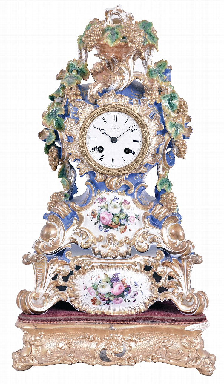 Grohe, a Paris, a three part, rococo style porcelain mantel clock with case by Jacob Petit, the clock and stand both decorated with molded and brightly painted naturalistic ornament, highlighted by bright gilding, all resting on a velvet lined,