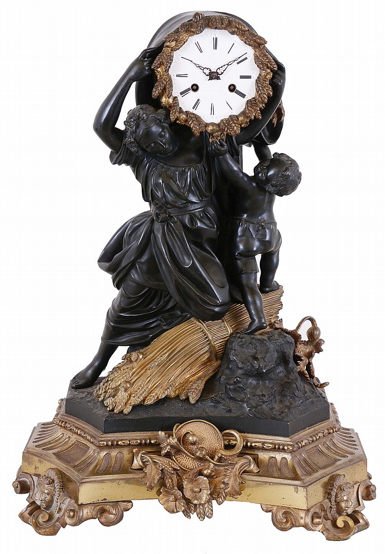 Hemon a Paris, figural mantel clock, gilt and patinated bronze case, the molded base with scroll feet set with Helios masks, the front with trophy, including poppies, acanthus, wheat, and tools of the harvest, and surmounted by a pair of nicely