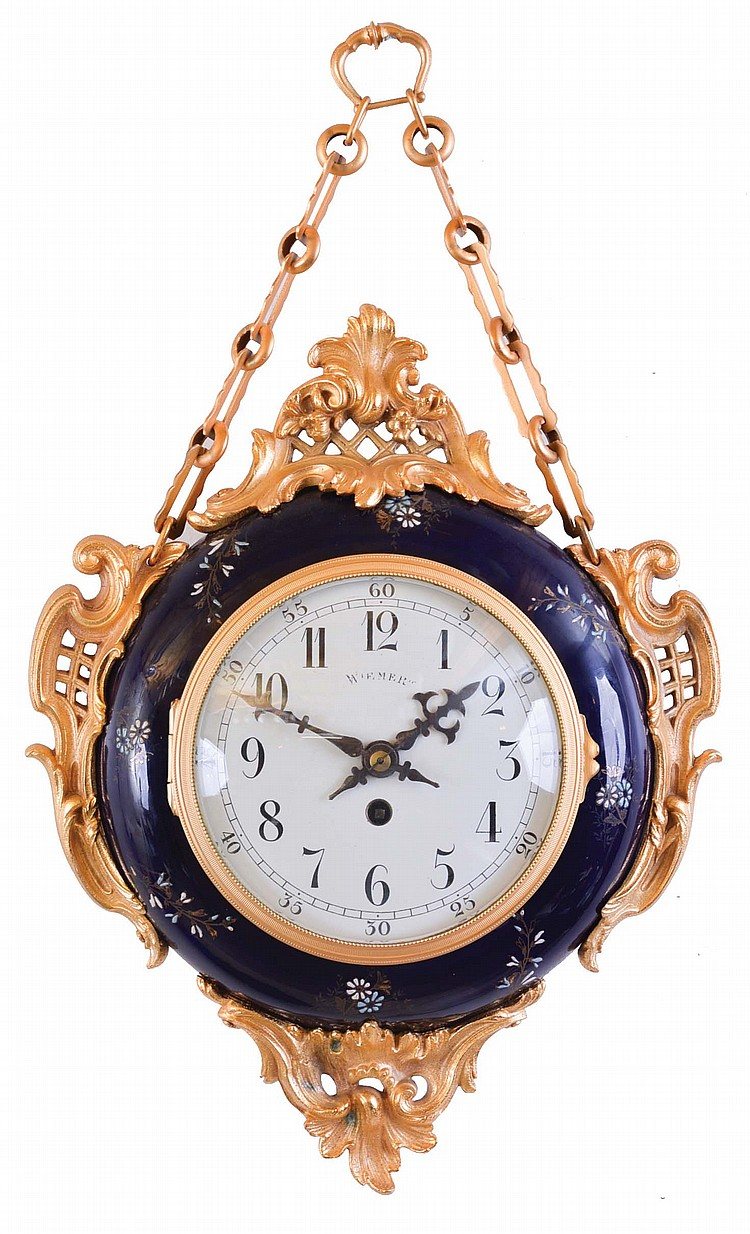 Wiemert, Paris, a two sided chatelaine clock, round, cobalt blue ceramic case with gilt and enamel foliage, and mounted with gilt naturalistic ornaments in the rococo style, gilt bezels with convex glasses, front and back with Arabic numeral white