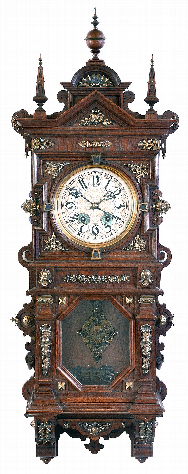 Lenzkirch, Germany, wall clock, the oak case richly ornamented with carving, moldings, and applied, cast brass elements, case top with central sphere and flanking obelisk finials, Arabic numeral silvered dial, blued steel hands, two train, 8 day