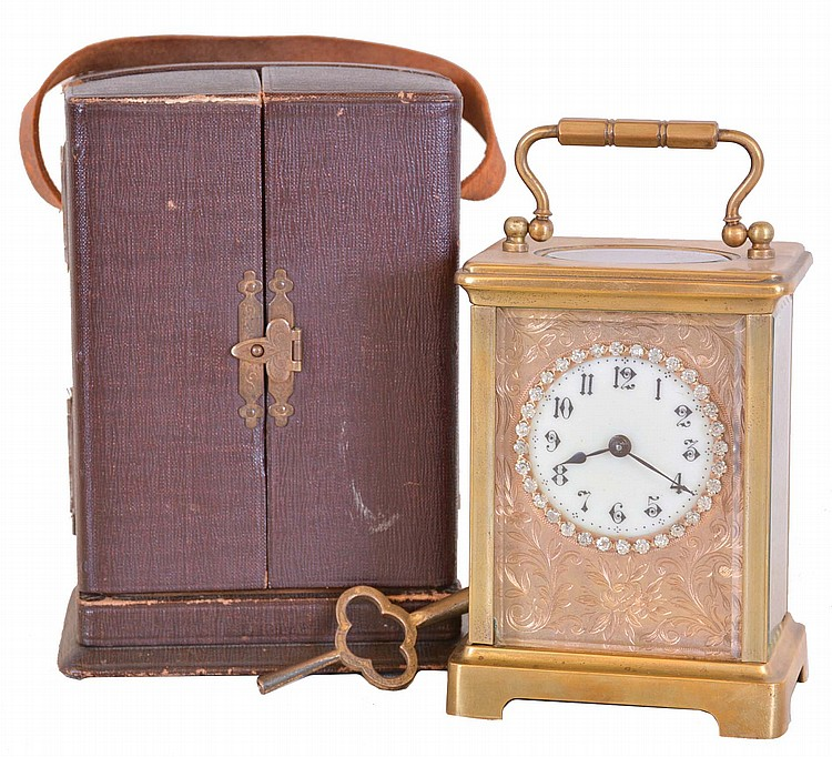 France, carriage clock, brass Corniche case with beveled glasses, Arabic numeral white enamel dial with engraved mask and brilliant set surround, 8 day timepiece movement with lever platform, and leather covered travel case