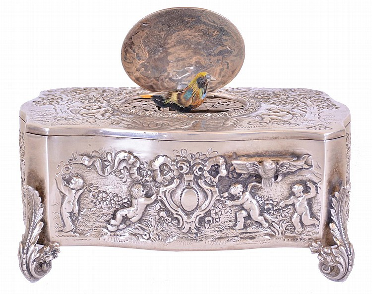 Germany, probably Karl Griesbaum, singing bird box, sterling silver serpentine form repousse case with landscapes inhabited by putti, on scrolled acanthus form feet, the cover with figure conducting a bird and putti orchestra, the multicolored bird