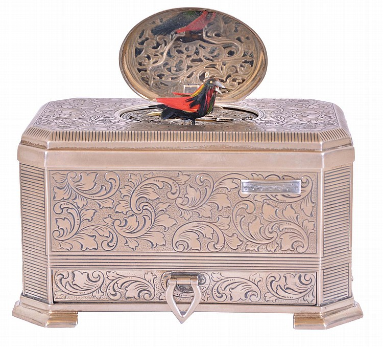 Mechanische Musikwerke Manufaktur, (MMM), Germany, singing bird box, the foliate engraved sterling silver case with canted corners, and a small drawer in the base, top with oval cover concealing a bird with brightly colored feathers, appearing and