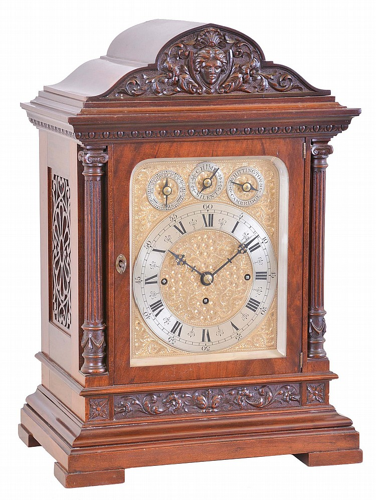 England, large bracket clock, polished mahogany architectural case, foliate carved panel above a molded, stepped base, fluted columns flanking the door, and supporting an egg and dart carved, molded cornice, the top with foliate carved paned and