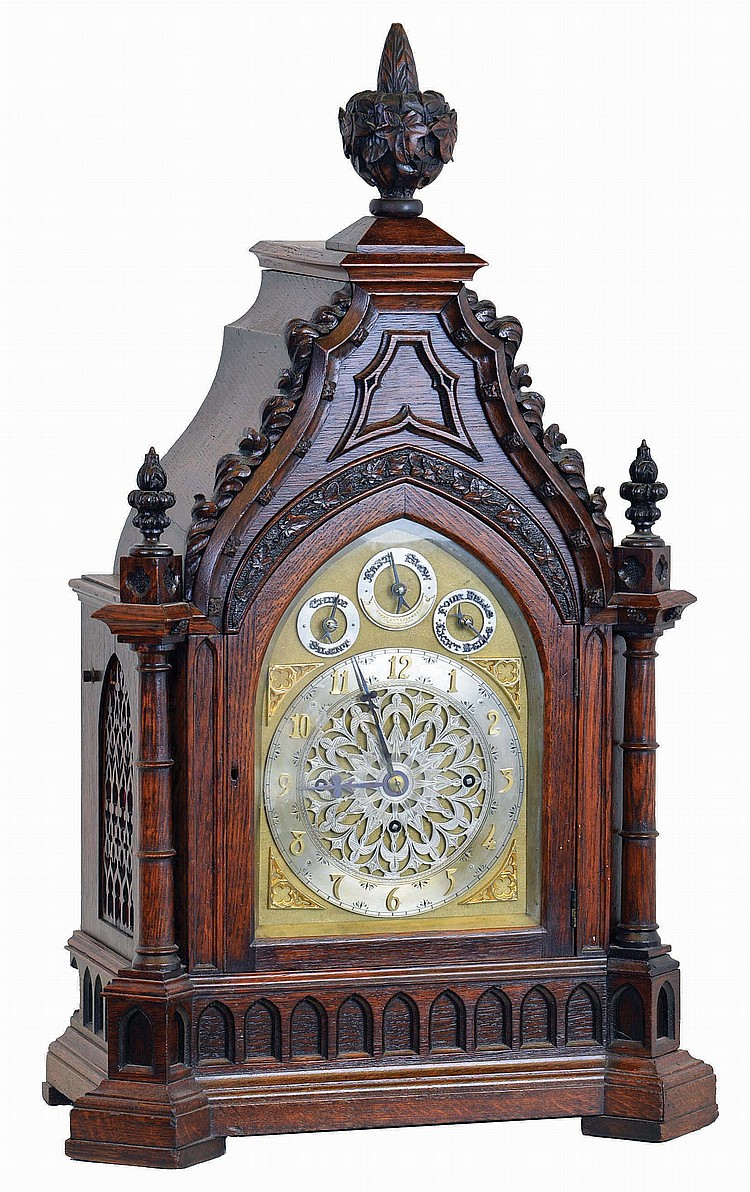 Frederick James Lockwood, West Norwood, London, large bracket clock in the Gothic style, carved oak case with buttress corners supporting turned columns, the molded base with lancet arch blind fret, lancet arch door below a carved lintel, the