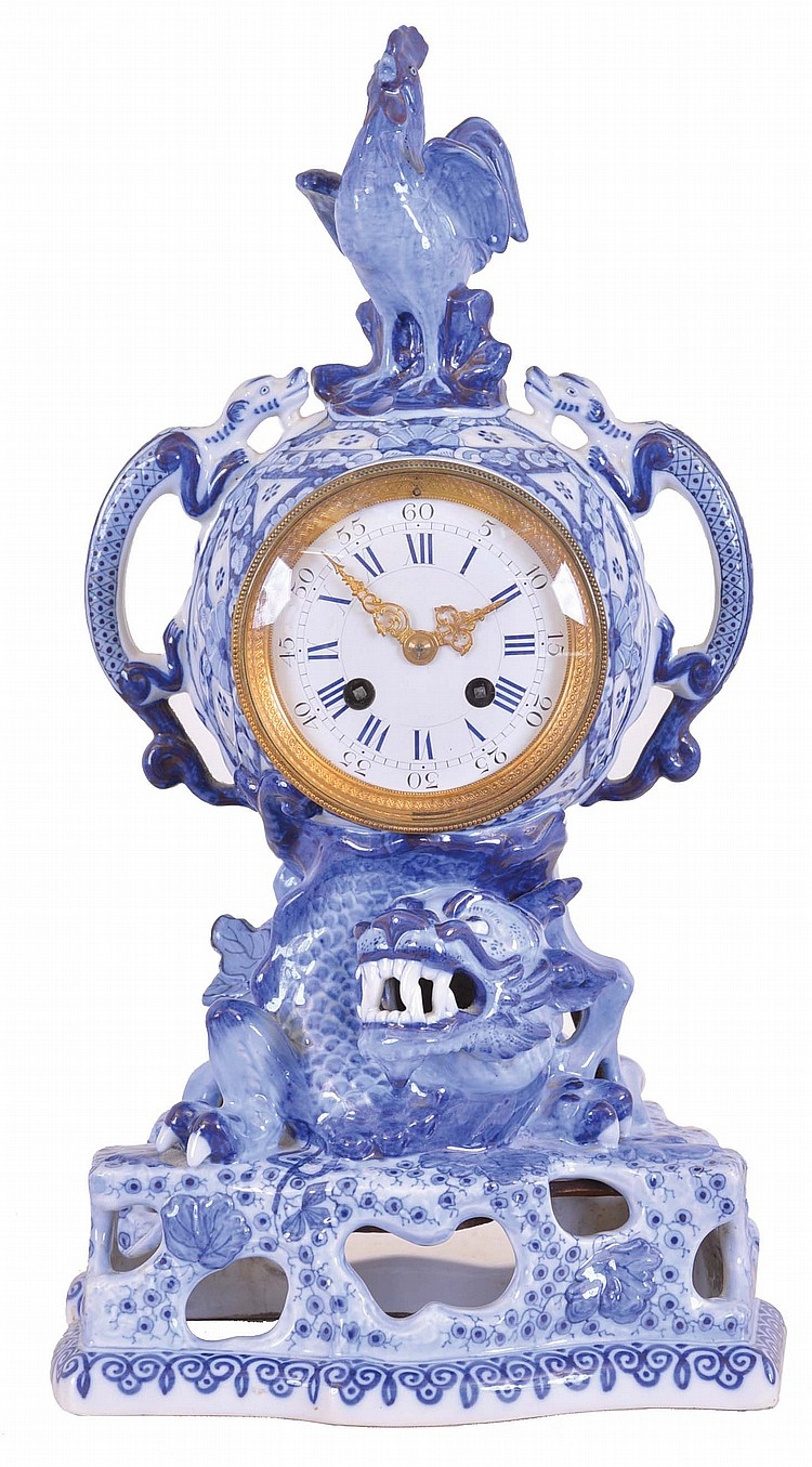 France, earthenware mantel clock, the openwork base with emerging dragon, case sides with giant salamanders, and surmounted by a crowing cock, decorated with blue transfer and free hand ornament in imitation of Canton porcelain, Roman numeral white