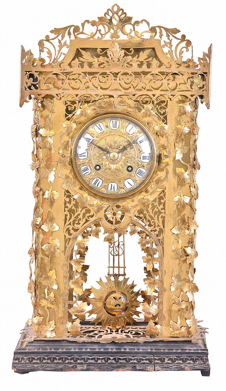 Mantel or table clock, the brass case with elaborate piercing, and applied brass leaves and vines, mounted to a similarly carved wooden base, the overall design seemingly inspired by the carving on Black Forest cuckoo clocks, cast dial with repousse
