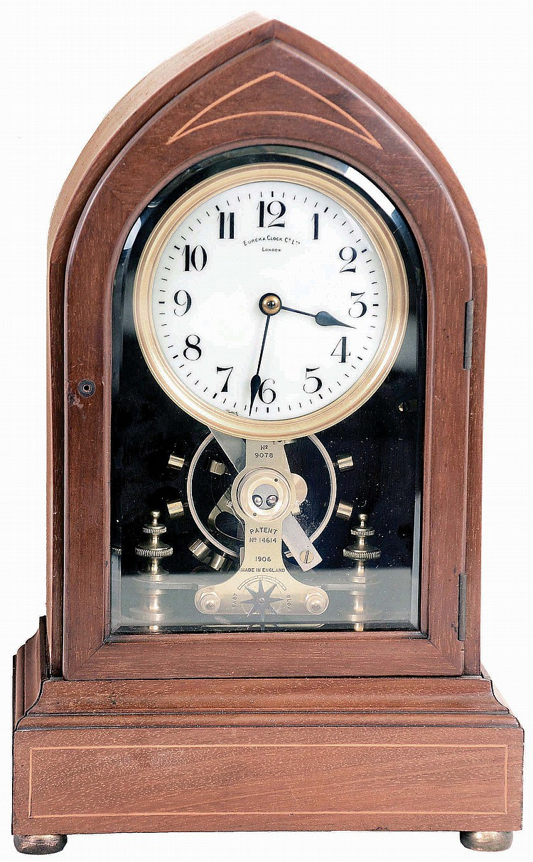 Eureka Clock Co. Ltd., London, England, battery powered mantel clock with oversized balance wheel movement in an inlayed Lancet or Beehive- style mahogany case with beveled glasses and cream porcelain dial, s#9078