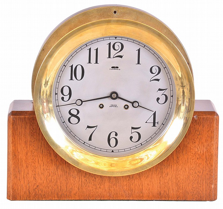 Chelsea Clock Co., Boston, Mass., 8 inch ships bell clock with custom made mahogany stand, cast brass case, Arabic numeral silvered dial, steel moon hands, 8 day lever movement with ships bell striking, serial #527160