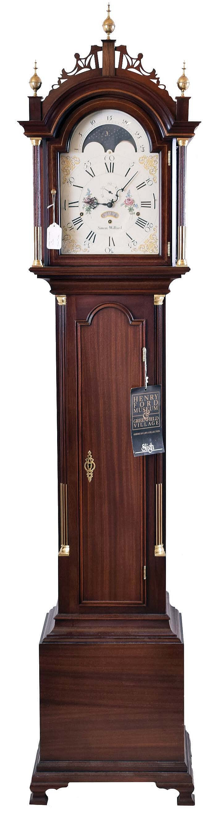 The Henry Ford Museum, Dearborn, Michigan reproduction Simon Willard, Boston, Mass., tall case clock, 8 day, time, strike and triple chime, weight driven movement in a mahogany Roxbury style case with three brass finials, fretwork top, fluted full