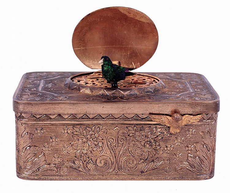 Switzerland or Germany, singing bird box, gilt case engraved with scrolls and foliate ornament, the oval lid concealing a bird with brightly colored feathers, appearing and performing on demand, the back with hinged panel revealing a small