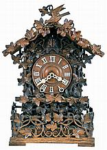 Johann Baptist Beha, Eisenbach, model 512 shelf cuckoo, nicely carved case with rustic railings covered in vines, roof with individually carved shakes and also trimmed with rustic ornament, vines, and a carved bird, Roman numeral wooden dial, pierced