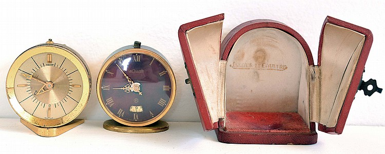 LeCoultre, Switzerland, two travel alarm clocks, one with red morocco case and convex dial, the other with red painted case and dial, both with lever escapements and alarms