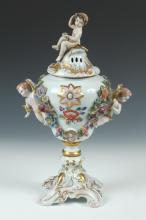 CONTINENTAL ROCOCO STYLE CAPODIMONTE URN WITH FIGURAL PUTTI HANDLES, 20th Century. Marked N with crown underglaze to base. - 15 1/2
