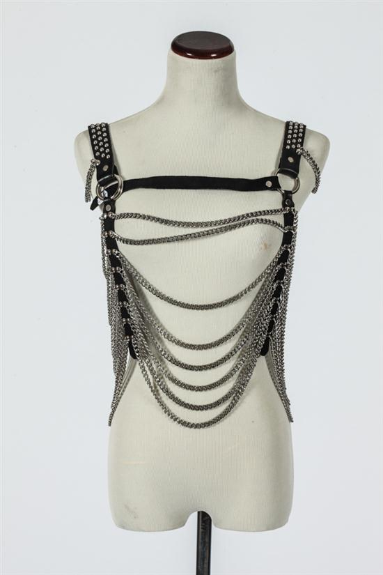 COSTUME CHAIN-LINK ACCESSORY WITH BLACK LEATHER STRAPS.