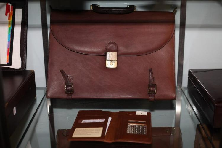 REDDISH BROWN BRIEFCASE WITH GOLD-TONE BUCKLES AND SMALL LEATHER CALCULATOR CASE.