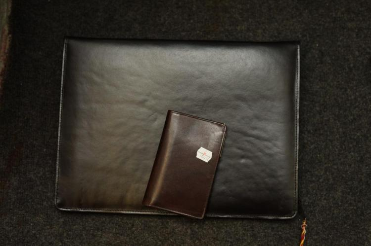 DARK BROWN LEATHER CASE WITH ZIP ENCLOSURE AND SMALL LEATHER ACCESSORY.