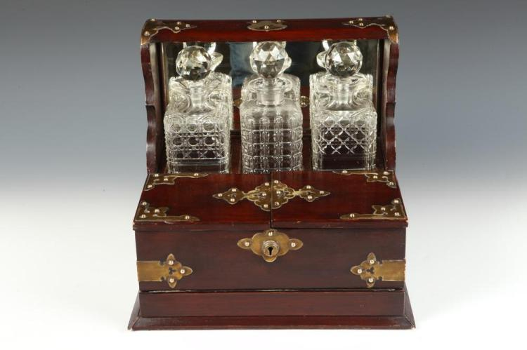 19TH CENTURY ENGLISH BRASS MOUNTED MAHOGANY TANTALUS WITH THREE CRYSTAL DECANTERS, 19th Century. Unmarked. - 13 1/2
