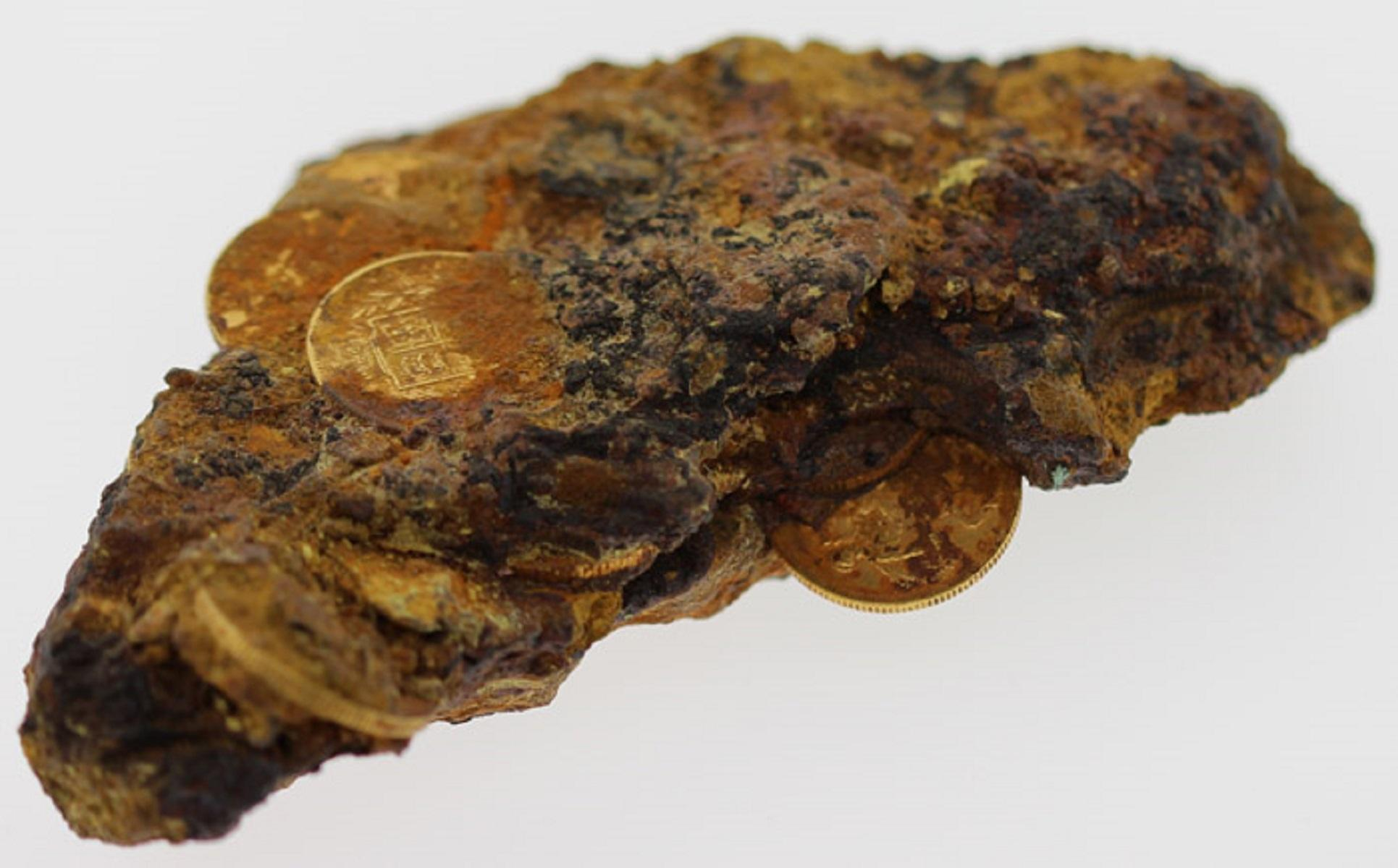 Sea-salvaged Gold Sovereigns (14 visible) subsumed into the surface of the iron holding safe recovered from ship-wreck of the Royal Mail Steamer 'Douro'