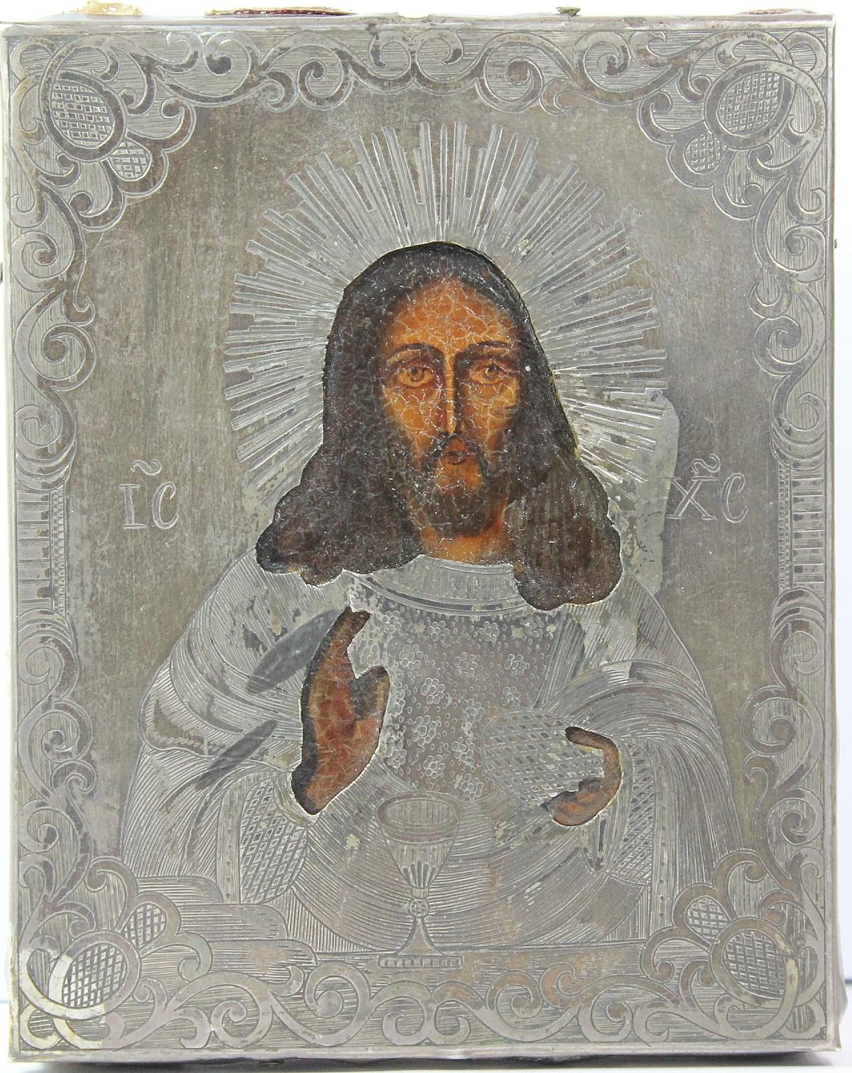 Naively painted rendition of Jesus Christ with an engraved and pierced silver overlay.