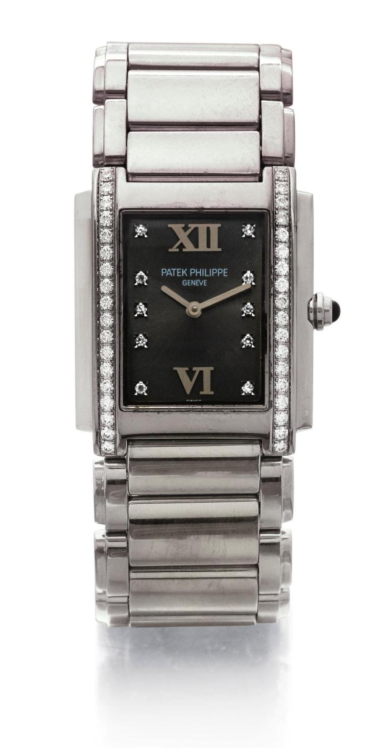 PATEK PHILIPPE | A STAINLESS STEEL AND DIAMOND SET RECTANGULAR WRISTWATCH WITH BRACELET REF 4910/10A MVT 1653918 CASE 4084199 TWENTY-4 MADE IN 1999