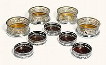 A SET OF FOUR GERMAN SILVER MOUNTED WINE BOTTLE COASTERS, BRAHMFELD & GUTRUF, HAMBURG, CIRCA 1850 |