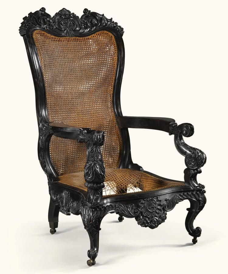 A MASSIVE CEYLONESE CARVED EBONY AND CANED ARMCHAIR, SRI LANKA, GALLE DISTRICT, MID-19TH CENTURY |