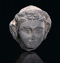 A GREY SCHIST HEAD OF A FEMALE ANCIENT REGION OF GANDHARA, KUSHAN PERIOD, 3RD CENTURY  